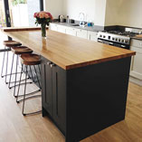 A large statement kitchen island that is topped with our 40mm Full Stave Oak surface.