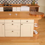 This beautiful kitchen island features a full stave oak worktop with a built in circular butcher's block at one end.