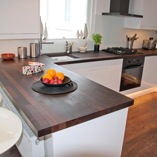 A modern kitchen that effectively utilises the contrast between the dark wood of the wenge worktops and the clean white finish of the kitchen cabinets.