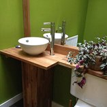 Oak worktop bathroom shelves with mounted sink bowl.