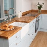 Oak worktops are perfectly complemented by timeless accessories such as ceramic Belfast sinks.