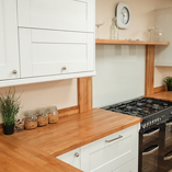 The prime oak worktop in this kitchen has been used to complement the white solid wood cabinets.