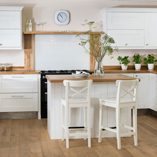The rich colour of the prime oak worktops combines beautifully with the white solid wood kitchen cabinets.
