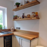 Here the solid oak floating shelves work wonderfully with the full stave oak kitchen worktops.