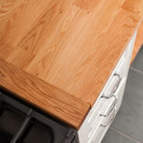 Here a stave is added to the end of the worktop to protect the wood from the heat of the oven.
