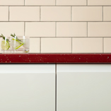 Our vivid red sparkle worktops contrast vibrantly against the white cabinet frontals and metro tiles.