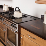 Here the wenge worktop and end panels creates a distinctive border around the kitchen cabinets.