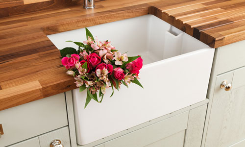 A kitchen with light grey cabinets, an oak worktop and a Belfast sink with flowers in