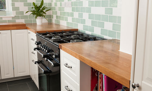 A kitchen with white cabinets, oak worktops and a mix of green and white subway tiles