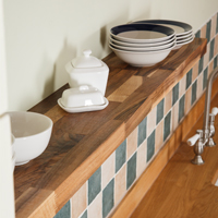 Pair walnut worktops with beautiful solid walnut floating shelving for a beautifully well-coordinated kitchen.