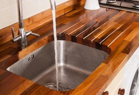 Walnut worktops with an undermounted sink cut-out, drainage grooves and a tap hole.