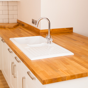 This white ceramic sink looks stunning against solid cherry worktops.